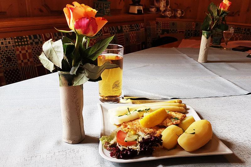 Es ist angerichtet. Geflügelsteak mit Kartoffeln, Spargel und Salatbeilage - neben einem Saft und einer Rose,