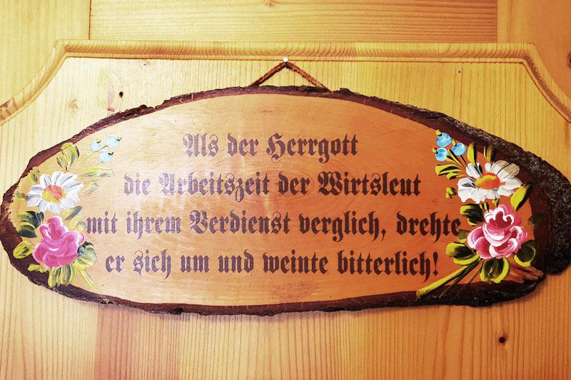 Ein Spruch und kunstvoll gestaltets Blumen auch einem Holzschild.