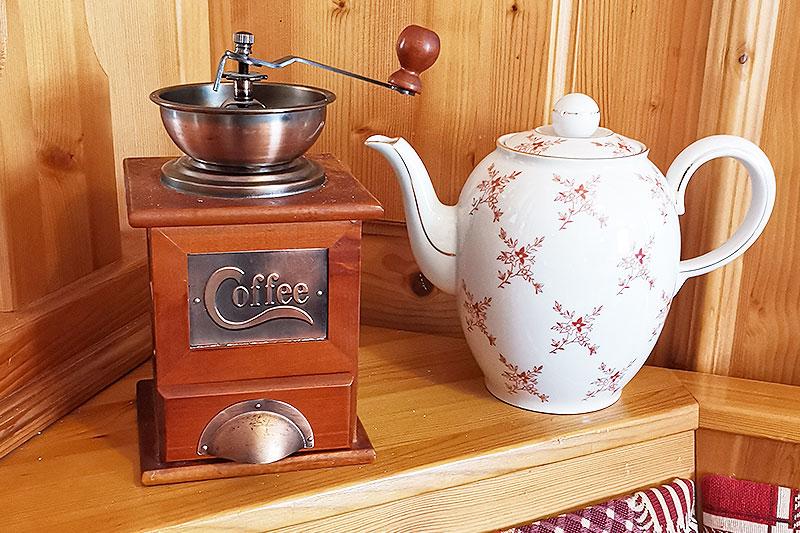Alte Kaffeekanne neben einer historischen Kaffeemühle.