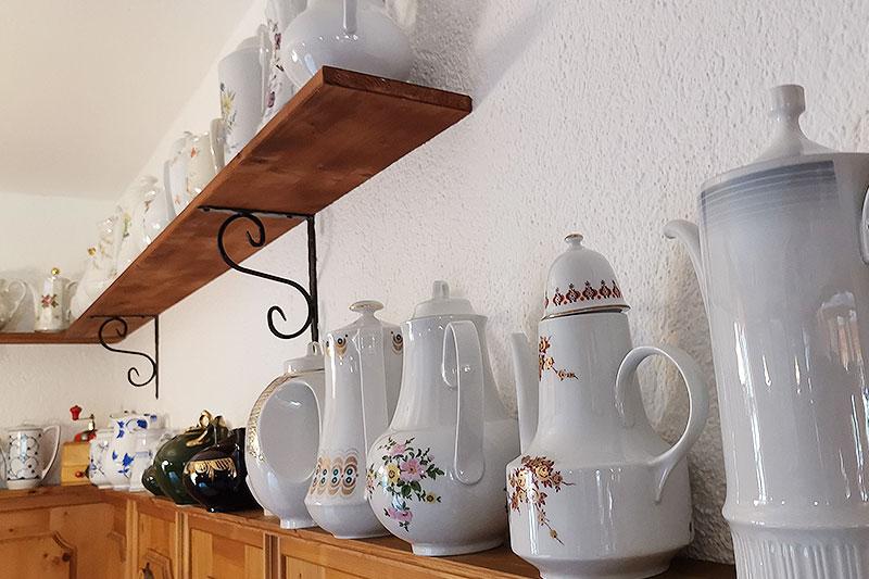 Zwei Regale voller historischer Kaffeekannen.