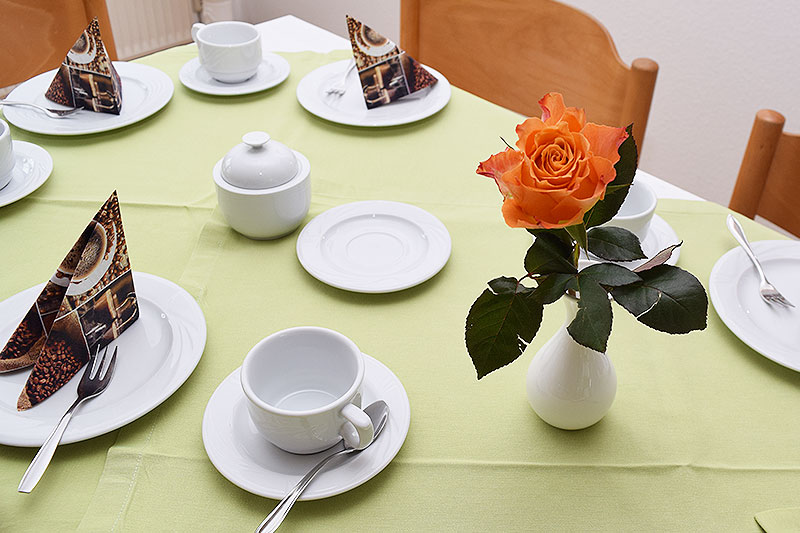 Liebevoll eingedeckter Kaffeetisch mit Rose.