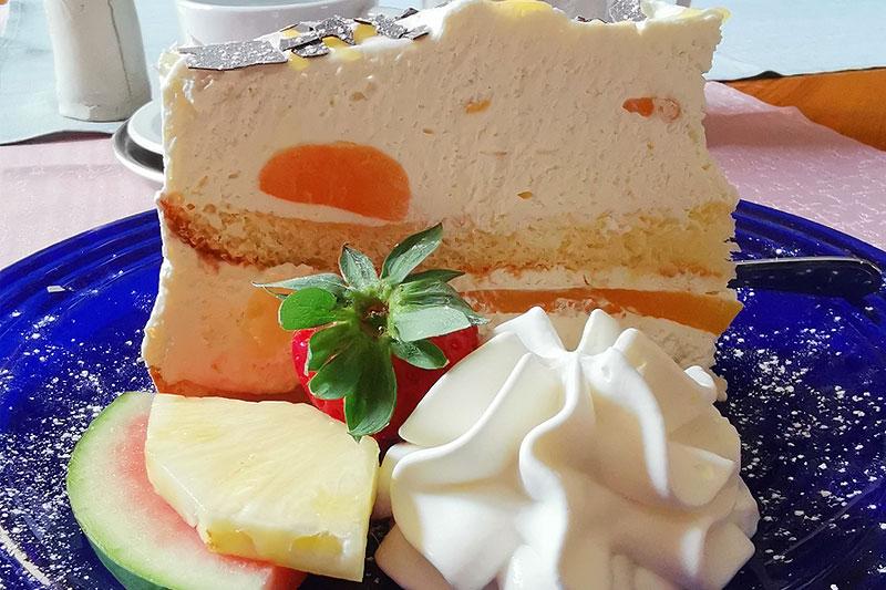 Ein Tortenstück serviert mit Schlagsahne und Melone
